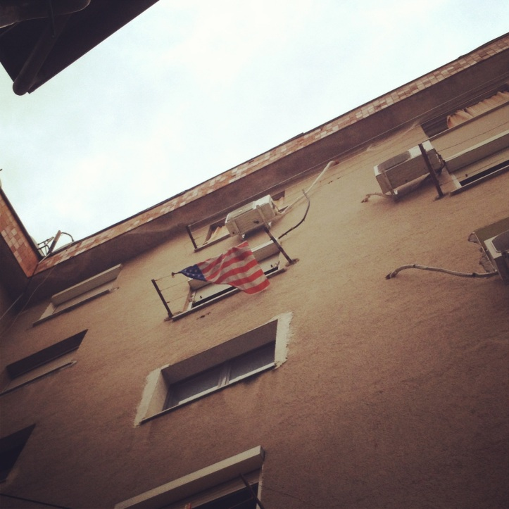 Flag hanging in a random apartment building in Tirana